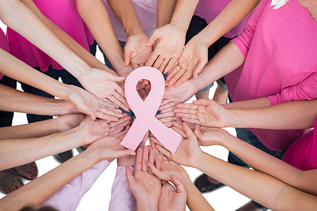 Hands joined in circle holding breast cancer struggle symbol